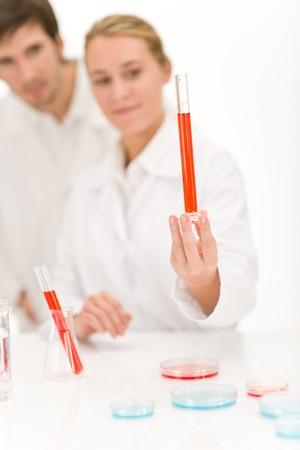 flu virus: Cient�ficos en el laboratorio - tubo de ensayo de virus de la gripe con l�quido rojo