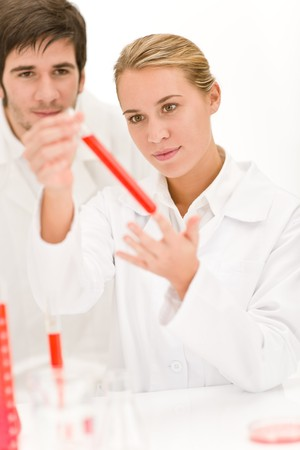 Scientists in laboratory - flu virus test tube with red liquid photo