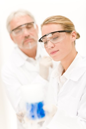 Chemistry experiment -  scientists in laboratory, wear protective eyewear photo