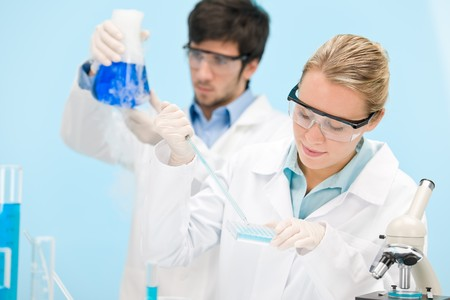 Flu virus experiment -  scientist in laboratory with microscope, wear protective eyewear Stock Photo - 8029305