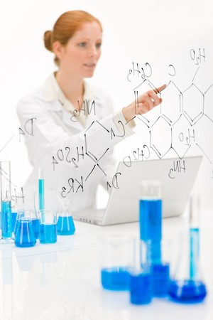 Woman scientist in laboratory with laptop and chemical formula photo