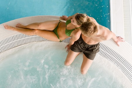 Top view - young couple relax in swimming pool sitting at bubble bath photo