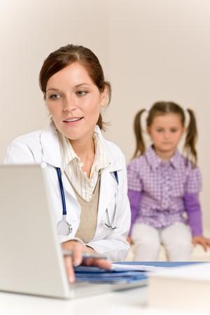 medico pediatra: Mujer m�dico receta para ni�o en cl�nica  Foto de archivo