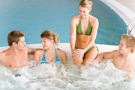 Swimming pool - young happy people relax in hot tub photo