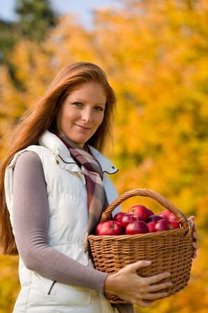 Autumn country - woman with wicker basket harvesting apple photo