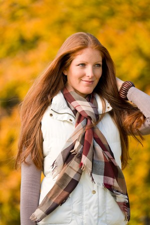 Autumn park - young attractive long red hair woman fashion photo