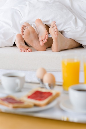 Luxury hotel honeymoon breakfast - couple in white bed together Stock Photo - 8259009