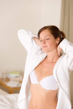 Morning bedroom - woman in bathrobe and bra waking up photo