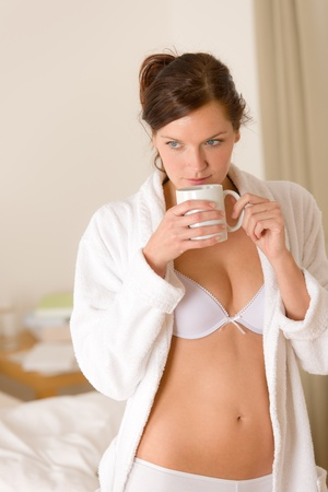 Morning bedroom - woman in bathrobe and lingerie with coffee waking up photo
