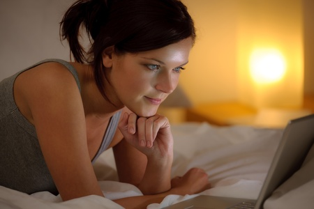 Bedroom evening - woman with laptop lying down in bed photo