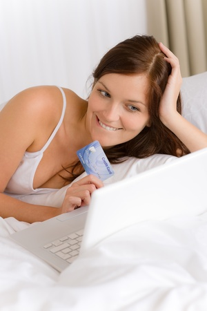 Home online shopping - woman with credit card lying down in white bed Stock Photo - 8259087