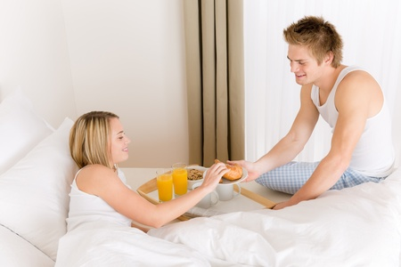 Luxury hotel honeymoon breakfast - couple in white bed together photo