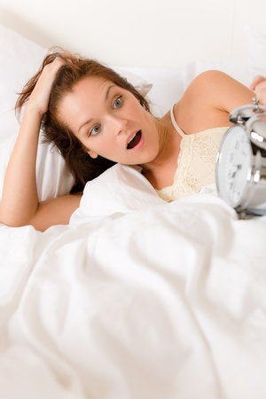 uyanmak: Bedroom - woman with alarm clock wake up in white bed Stok Fotoğraf