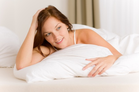 Bedroom - happy woman in white bed waking up photo
