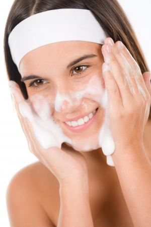 Teenager problem skin care - woman wash face with cleansing foam photo