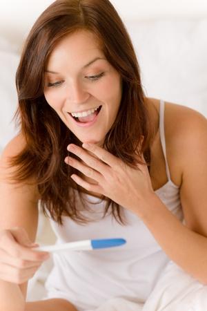 prueba de embarazo: Prueba de embarazo - mujer sorprende feliz, resultado positivo