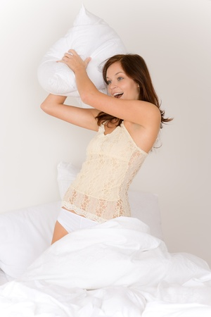 Pillow fight: PIllow fight - young woman in bed having fun