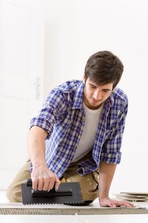 Home improvement, renovation - handyman laying tile, trowel with mortar Stock Photo - 8374869