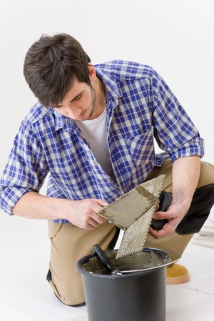 Home improvement, renovation - handyman laying tile, trowel with mortar Stock Photo - 8374818