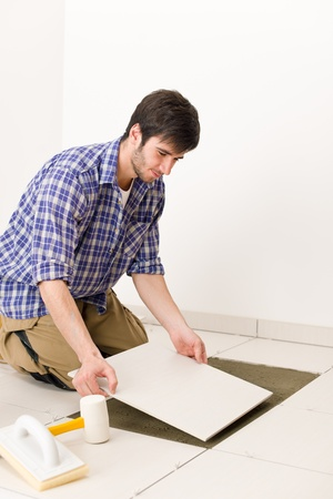 Home improvement, renovation - handyman laying tile, trowel with mortar Stock Photo - 8374879