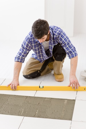 Home tile improvement - handyman with level laying down tile floor Stock Photo - 8374878
