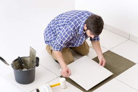 lying on the floor: Home improvement, renovation - handyman laying tile, trowel with mortar