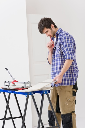 Home improvement - handyman cut ceramic tile in workshop photo