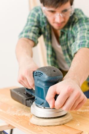 Home improvement - handyman sanding wooden floor in workshop photo