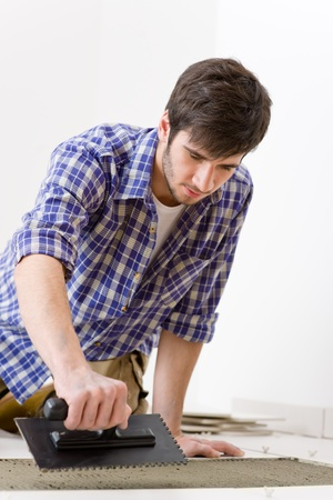 Home improvement, renovation - handyman laying tile, trowel with mortar Stock Photo - 8417855