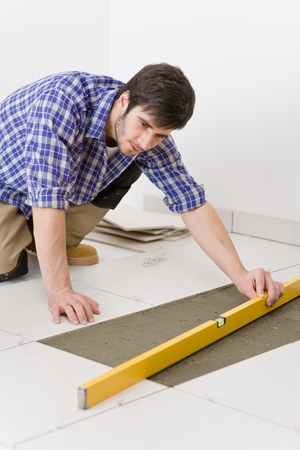 Home tile improvement - handyman with level laying down tile floor Stock Photo - 8417851