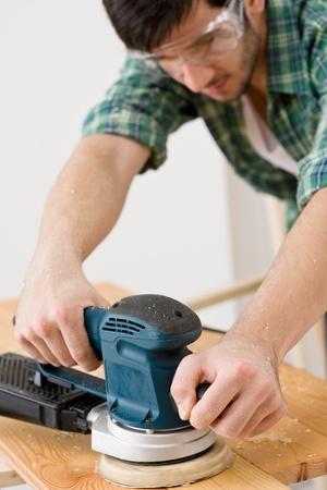 Home improvement - handyman sanding wooden floor in workshop Stock Photo - 8417836