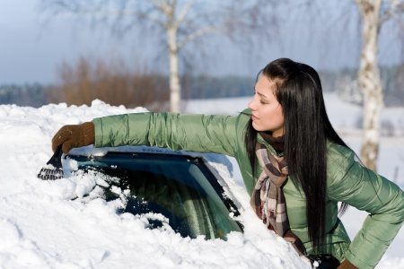 Winter car - woman remove snow from windshield with ice scraper photo