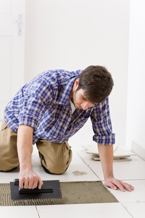 Home improvement, renovation - handyman laying tile, trowel with mortar Stock Photo - 8442551