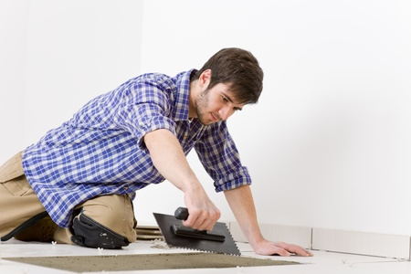 Home improvement, renovation - handyman laying tile, trowel with mortar Stock Photo - 8442553