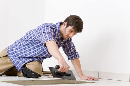 Home improvement, renovation - handyman laying tile, trowel with mortar Stock Photo - 8442553