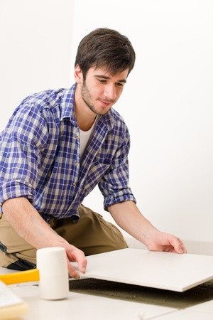 Home improvement, renovation - handyman laying tile, trowel with mortar Stock Photo - 8442547
