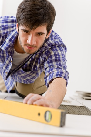 Home tile improvement - handyman with level laying down tile floor Stock Photo - 8442550