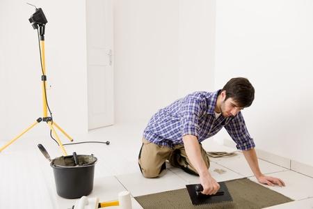 overhaul: Home improvement, renovation - handyman laying tile, trowel with mortar