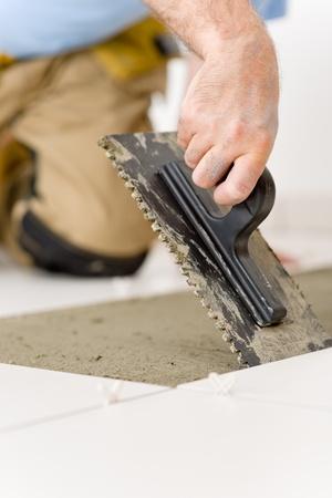 Home improvement, renovation - handyman laying tile, trowel with mortar Stock Photo - 8546345