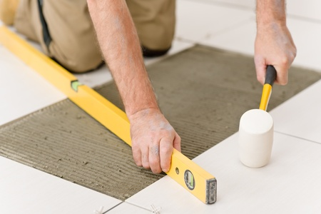 Home improvement, renovation - handyman laying tile with level photo