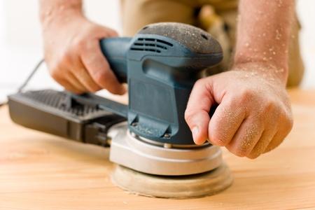 Home improvement - handyman sanding wooden floor in workshop Stock Photo