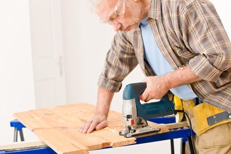 Home improvement - handyman cut wood with jigsaw in workshop photo