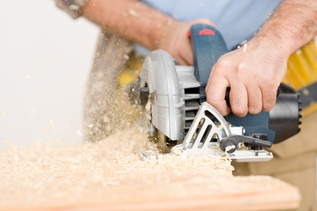 Home improvement - handyman cut wood with jigsaw in workshop photo