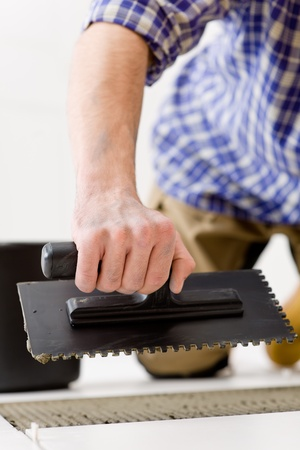 Home improvement, renovation - handyman laying tile, trowel with mortar Stock Photo - 8546392