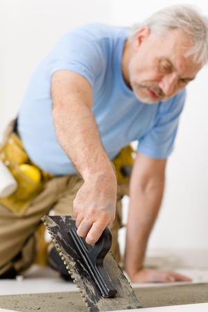 Home improvement, renovation - handyman laying tile, trowel with mortar Stock Photo - 8546391