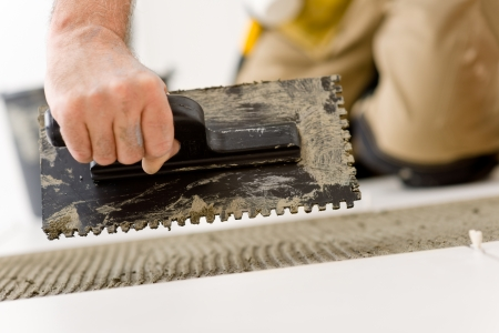 home renovations: Home improvement, renovation - handyman laying tile, trowel with mortar