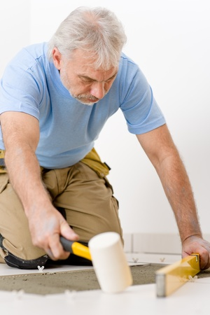 Home improvement, renovation - handyman laying tile with level Stock Photo - 8546388