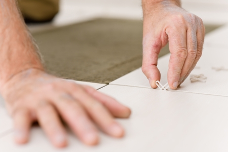 Home improvement, - close-up of handyman placing tile spacer photo