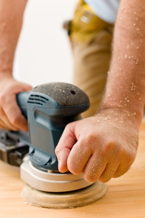 Home improvement - handyman sanding wooden floor in workshop photo