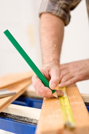 Home improvement - close-up of handyman measure wooden floor Stock Photo - 8546387